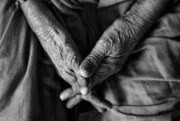 Wrinkled hands of an old person